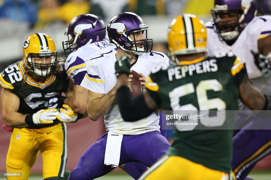 Christian Ponder of the Minnesota Vikings drops back to pass between Clay Matthews and Julius Peppers of the Green Bay Packers during the third...