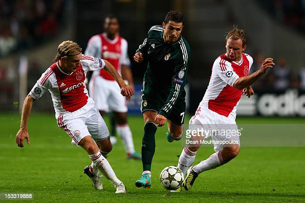Christian Poulsen and Siem De Jong of Ajax tackle Cristiano Ronaldo of Real during the UEFA Champions League Group D match between Ajax Amsterdam and...