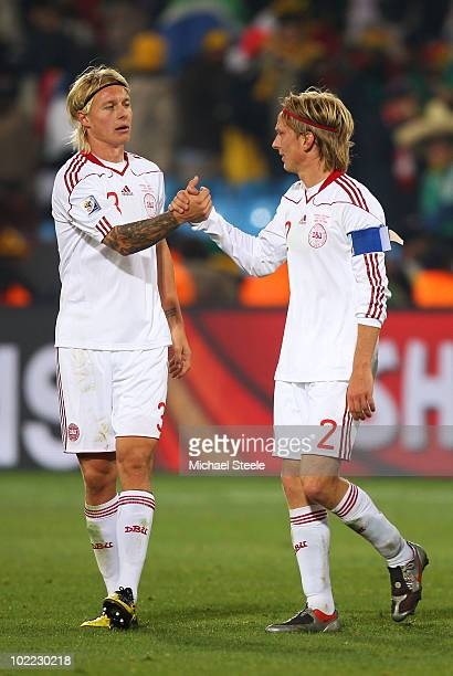 Christian Poulsen and Simon Kjaer of Denmark celebrate victory in the 2010 FIFA World Cup South Africa Group E match between Cameroon and Denmark at...