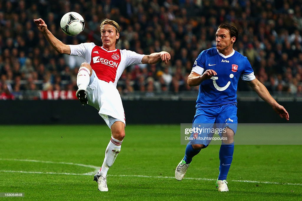 <a gi-track='captionPersonalityLinkClicked' href=/galleries/search?phrase=Christian+Poulsen&family=editorial&specificpeople=228068 ng-click='$event.stopPropagation()'>Christian Poulsen</a> (L) of Ajax clears the ball away from Robbert Schilder of Twente during the Eredivisie match between Ajax Amsterdam and FC Twente at Amsterdam Arena on September 29, 2012 in Amsterdam, Netherlands.