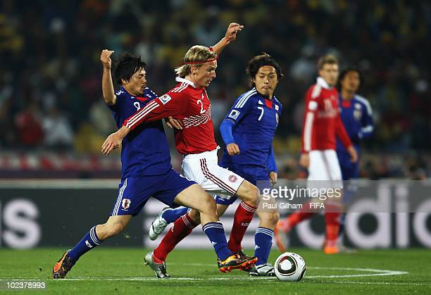 Christian Poulsen of Denmark is tackled by Daisuke Matsui of Japan during the 2010 FIFA World Cup South Africa Group E match between Denmark and...