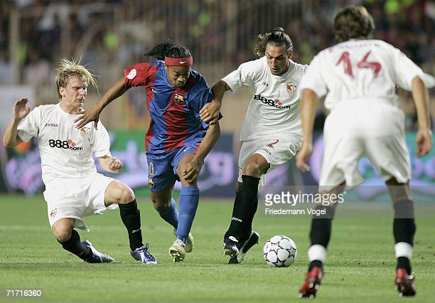 Christian Poulsen of Sevilla tussels for the ball with Ronaldinho of Barcelona Javi Navarro and Julien Escude of Sevilla during the UEFA Super Cup...