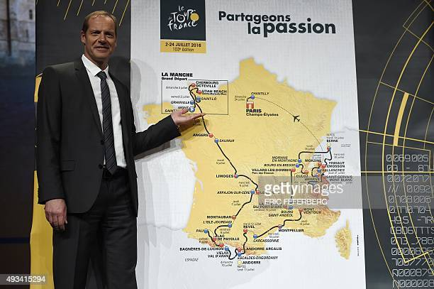 Christian Prudhomme director general of the Tour de France poses next to a map showing the official route of the 2016 Tour de France cycling race...