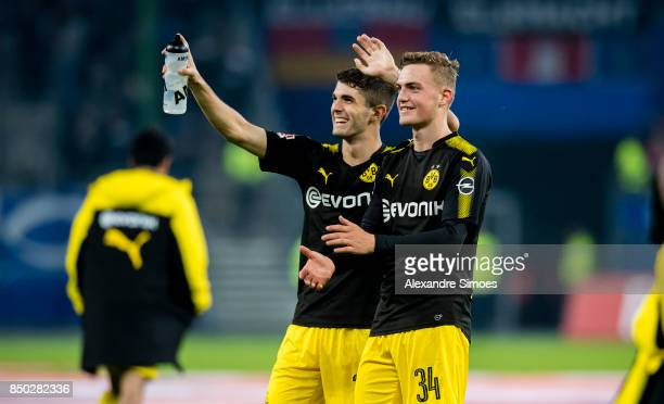 Christian Pulisic and Jacob Bruun Larsen of Borussia Dortmund celebrate the win after the final whistle during the Bundesliga match between Hamburger...