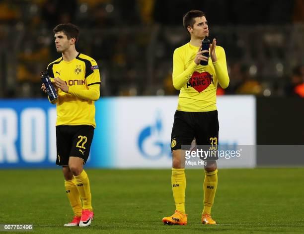Christian Pulisic and Julian Weigl of Borussia Dortmund applaud the fans following the UEFA Champions League Quarter Final first leg match between...