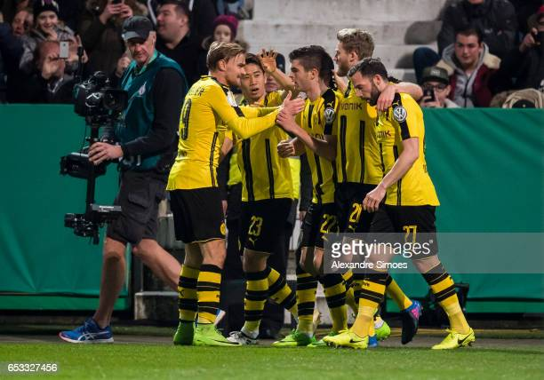 Christian Pulisic of Borussia Dortmund celebrates scoring the opening goal together with his team mates during the DFB Cup Quarter Final match...
