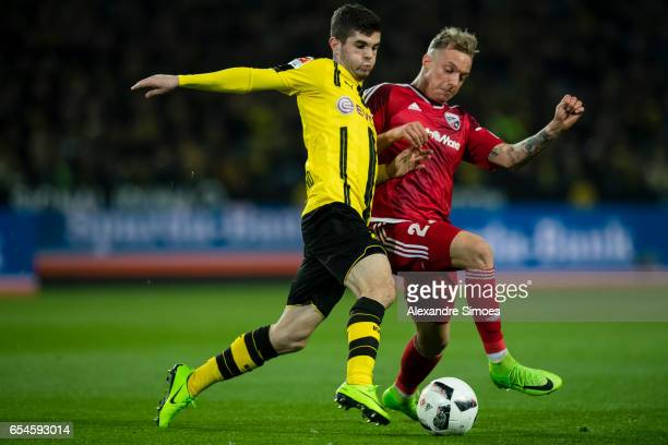 Christian Pulisic of Borussia Dortmund challenges Sonny Kittel of FC Ingolstadt 04 during the Bundesliga match between Borussia Dortmund and FC...