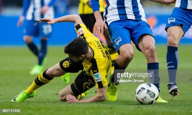 Christian Pulisic of Borussia Dortmund gets challenged Niklas Stark of Hertha BSC during the Bundesliga match between Hertha BSC and Borussia...