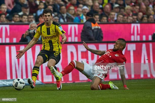 Christian Pulisic of Dortmund and Arturo Vidal of Munich battle for the ball during the Bundesliga match between Bayern Muenchen and Borussia...
