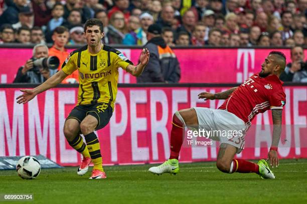 Christian Pulisic of Dortmund and Arturo Vidal of Munich controls the ball during the Bundesliga match between Bayern Muenchen and Borussia Dortmund...