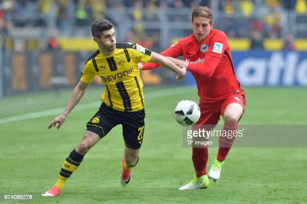 Christian Pulisic of Dortmund and Bastian Oczipka of Frankfurt battle for the ball during the Bundesliga match between Borussia Dortmund and...