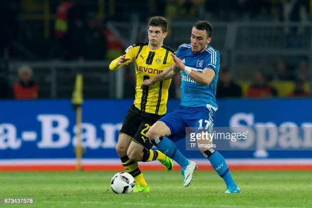 Christian Pulisic of Dortmund and Filip Kostic of Hamburg battle for the ball during the Bundesliga match between Borussia Dortmund and Hamburger SV...