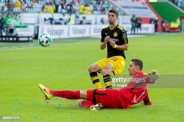 Christian Pulisic of Dortmund and Goalkeeper Koen Casteels of Wolfsburg battle for the ball during to the Bundesliga match between VfL Wolfsburg and...