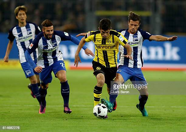 Christian Pulisic of Dortmund and Marvin Plattenhardt and Valentin Stocker of Berlin battle for the ball during the Bundesliga match between Borussia...