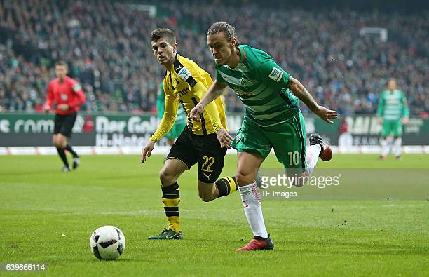 Christian Pulisic of Dortmund and Max Kruse of Bremen battle for the ball during the Bundesliga match between Werder Bremen and Borussia Dortmund at...