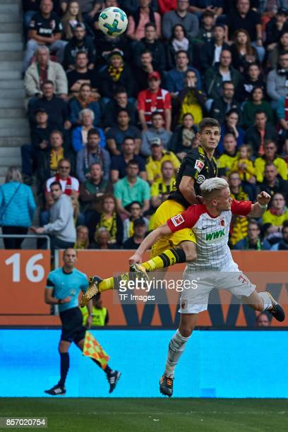 Christian Pulisic of Dortmund and Philipp Max of Augsburg battle for the ball during the Bundesliga match between FC Augsburg and Borussia Dortmund...