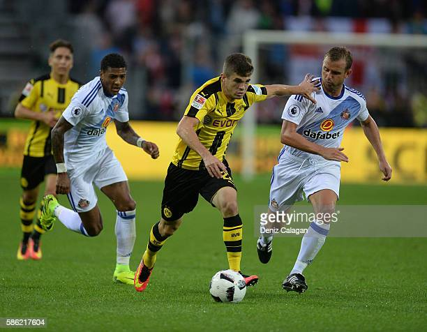 Christian Pulisic of Dortmund challenges Patrick Van Aanmolt of Sunderland and Lee Cattermole of Sunderland during the friendly match between AFC...