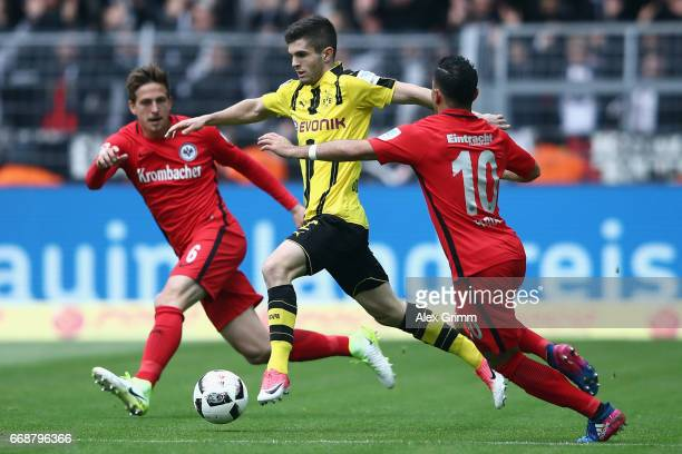 Christian Pulisic of Dortmund is challenged by Bastian Oczipka and Marco Fabian of Frankfurt during the Bundesliga match between Borussia Dortmund...