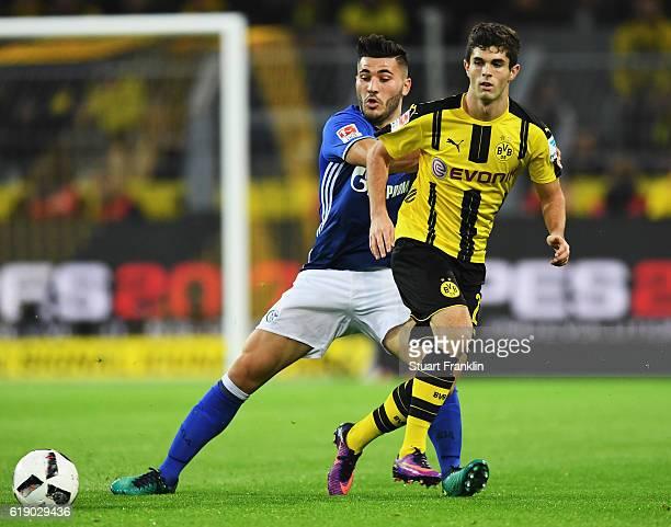 Christian Pulisic of Dortmund is challenged by Sead Kolasinac of Schalke during the Bundesliga match between Borussia Dortmund and FC Schalke 04 at...