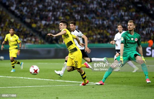 Christian Pulisic of Dortmund is fouled by goalkeeper Lukas Hradecky of Frankfurt during the DFB Cup final match between Eintracht Frankfurt and...