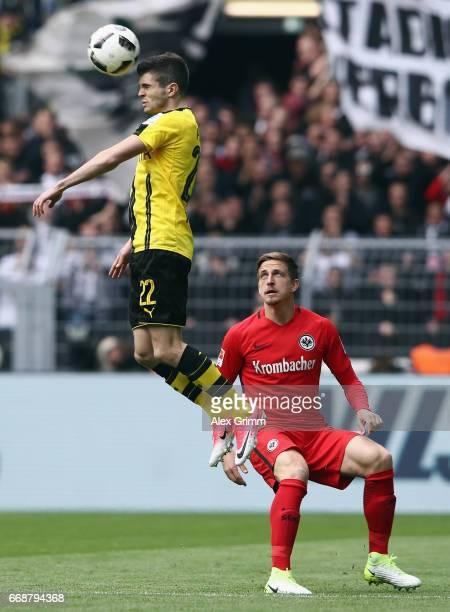 Christian Pulisic of Dortmund outjumps Bastian Oczipka of Frankfurt during the Bundesliga match between Borussia Dortmund and Eintracht Frankfurt at...