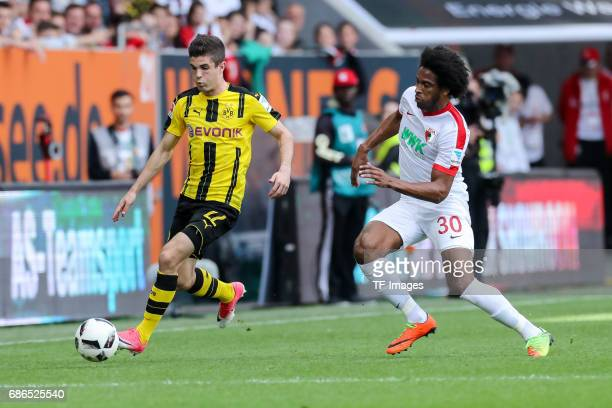 Christian Pulisic of Dortmund und Caiuby Francisco da Silva of Augsburg battle for the ball during the Bundesliga match between FC Augsburg and...