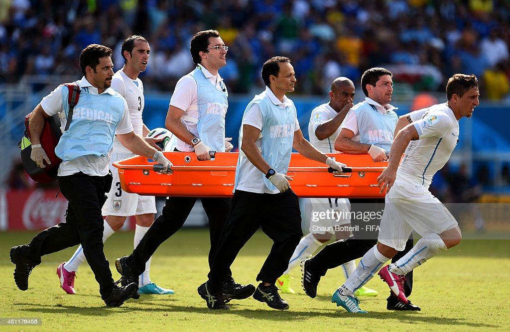 Christian Rodriguez of Uruguay helps to carry on the stretcher during the 2014 FIFA World Cup Brazil Group D match between Italy and Uruguay at Estadio das Dunas on June 24, 2014 in Natal, Brazil.