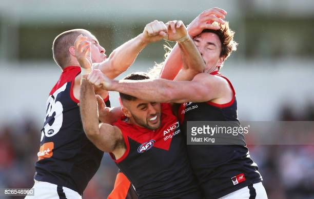 Christian Salem of the Demons competes for the ball with Tom McDonald and Michael Hibberd of the Demons during the round 20 AFL match between the...