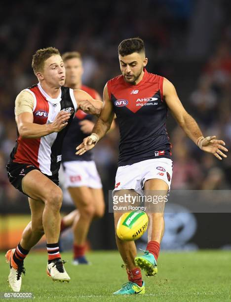 Christian Salem of the Demons kicks whilst being tackled Jack Billings of the Saints during the round one AFL match between the St Kilda Saints and...