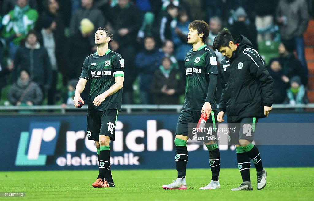 Christian Schulz Hiroki Sakai and Hotaru Yamaguchi of Hannover look dejected during the Bundesliga match between Werder Bremen and Hannover 96 at...