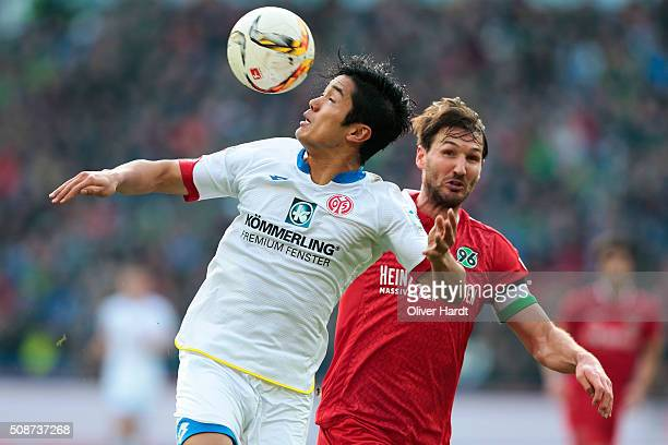 Christian Schulz of Hannover and Yoshinori Muto of Mainz compete for the ball during the first Bundesliga match between Hannover 96 and 1 FSV Mainz...