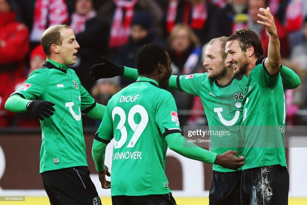 Christian Schulz of Hannover celebrates his team's first goal with team mates Konstantin Rausch Mame Biram Diouf and Jan Schlaudraff during the...