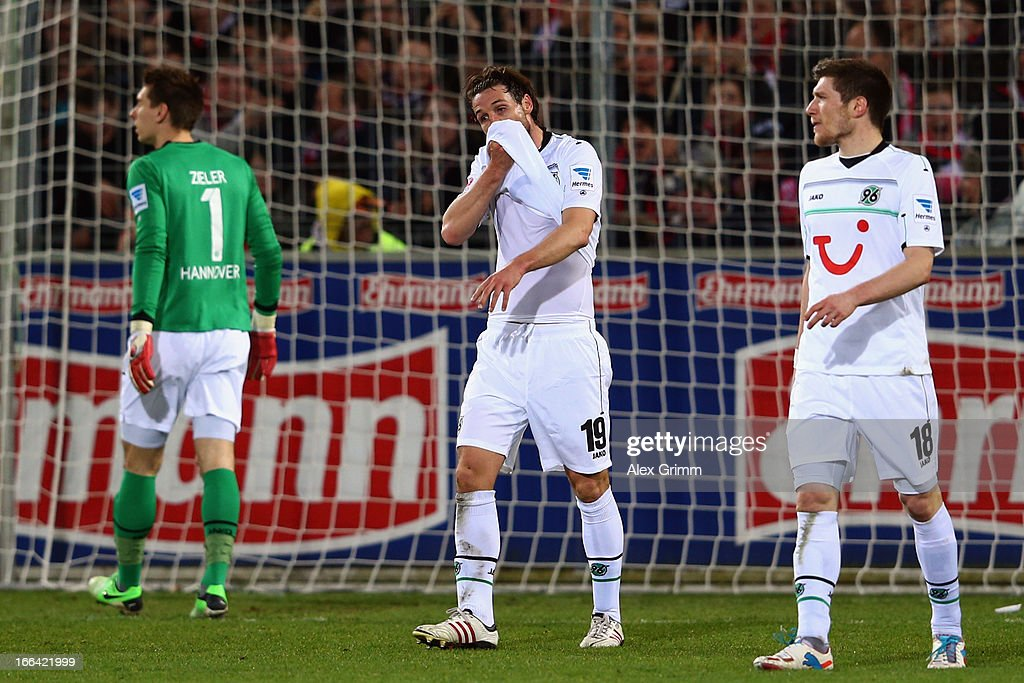 <a gi-track='captionPersonalityLinkClicked' href=/galleries/search?phrase=Christian+Schulz&family=editorial&specificpeople=228730 ng-click='$event.stopPropagation()'>Christian Schulz</a> (C) of Hannover reacts after scoring an own-goal during the Bundesliga match between SC Freiburg and Hannover 96 at MAGE SOLAR Stadium on April 12, 2013 in Freiburg im Breisgau, Germany.