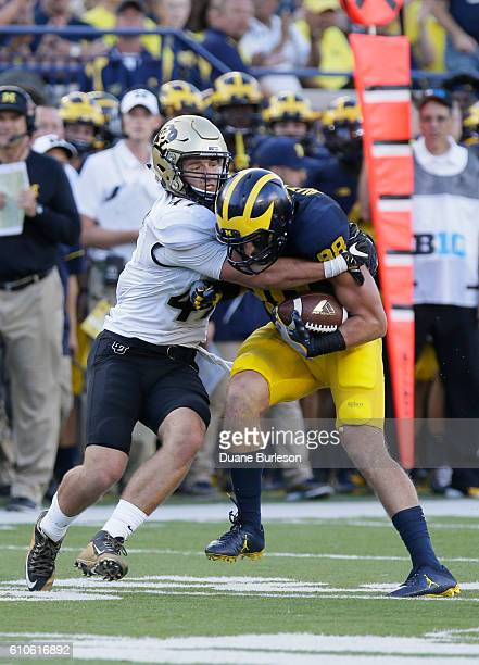 Christian Shaver of the Colorado Buffaloes tackles Jake Butt of the Michigan Wolverines after a first down catch at Michigan Stadium on September 17...