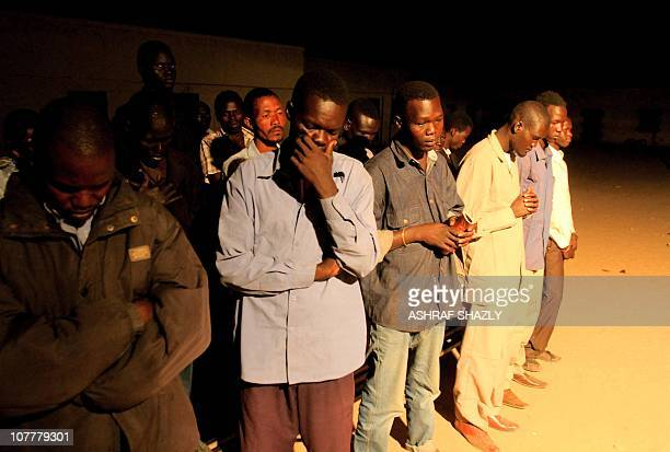 Christian southern Sudanese pray during Christmas mass in the Soba district of southern Khartoum on December 24 as parishioners seek comfort fearful...