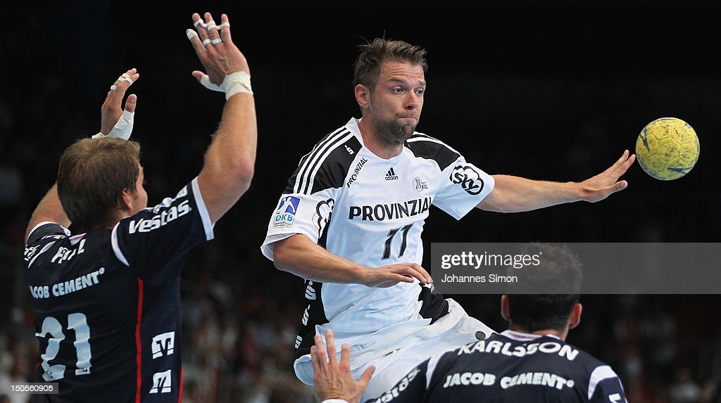 Christian Sprenger (C) of Kiel is challenged by Jacob Heinl (L) and Tobias Karlsson (R) of Flensburg during the Handball Supercup match between THW Kiel and SG Flensburg Handewitt at Olympia Eishalle on August 21, 2012 in Munich, Germany.