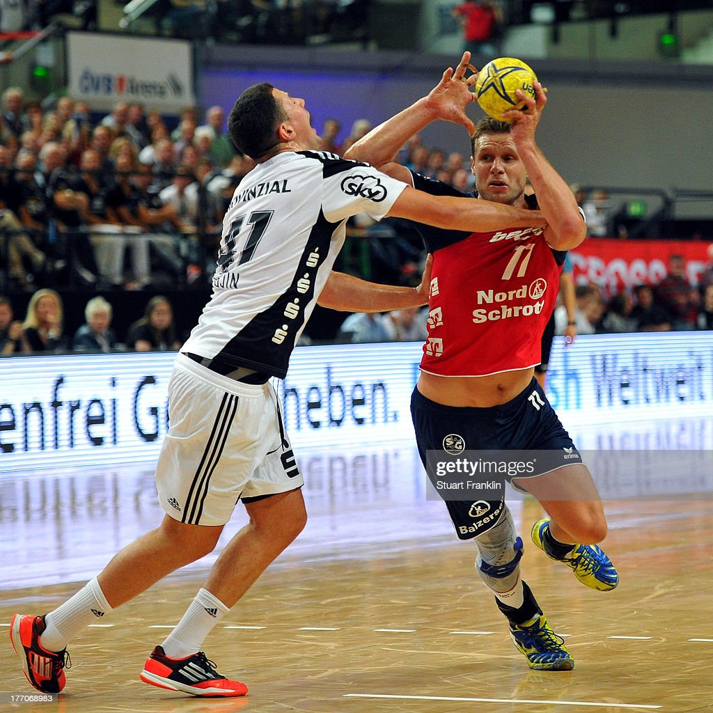 Christian Sprenger of Kiel is challenged by Michael Knudsen of Flensburg during th DKB supercup match between THW Kiel and Flensburg Handewitt at OVB arena on August 20, 2013 in Bremen, Germany.