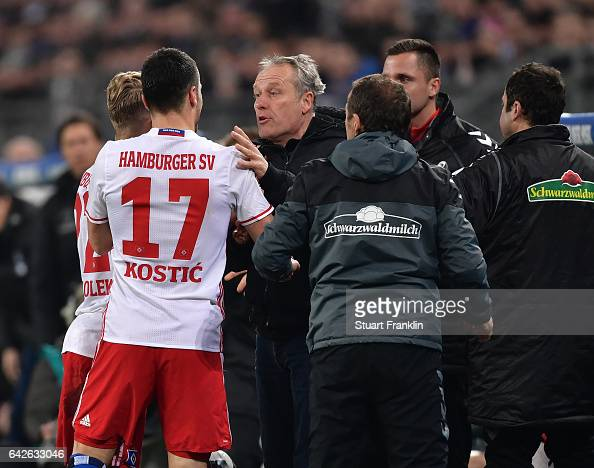 Christian Streich head coach of Freiburg clashes with Filip Kostic of Hamburg during the Bundesliga match between Hamburger SV and SC Freiburg at...