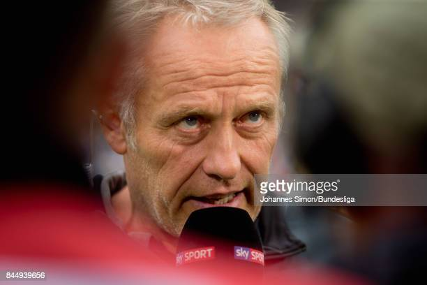 Christian Streich head coach of Freiburg gives a TV interview prior to the Bundesliga match between SportClub Freiburg and Borussia Dortmund at...