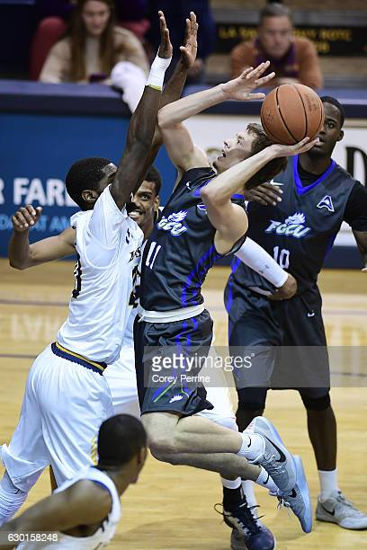 Christian Terrell of the Florida Gulf Coast Eagles attempts a shot over BJ Johnson as Demetrius Henry both of the La Salle Explorers smiles during...
