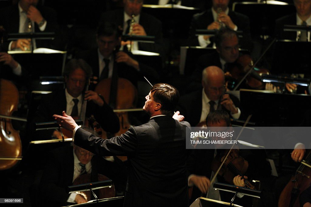 Christian Thielemann conducts an orchestra during a memorial service for Wolfgang Wagner the grandson of composer Richard Wagner in the southern...