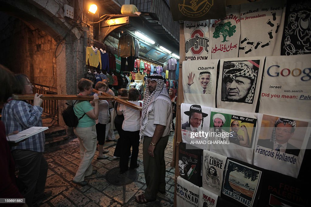 Christian tourists carry a cross past a souvenir shop in Jerusalem's old city displaying t-shirts for sale among them one of US Republican presidential candidate Mitt Romney wearing a Jewish Orthodox hat (L), one of US President Barak Obama under his 2008 campaign slogan next to a portrait of assassinated al-Qaeda leader Osama Ben Laden and and the latter wearing a traditional Arab headscarf, on November 6, 2012. AFP PHOTO/AHMAD GHARABLI