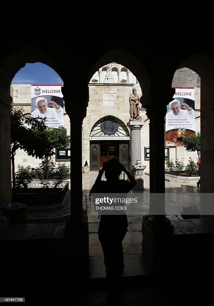 Christian tourists take a picture of a banner bearing portraits of Pope Francis on May 18, 2014, inside the yard of Saint Catherine Church in the Church of Nativity, in the West Bank Town of Bethlehem.The pope's visit is scheduled to begin in Jordan on May 24, and he is then due to spend two days in the Holy Land from May 25. AFP PHOTO / THOMAS COEX