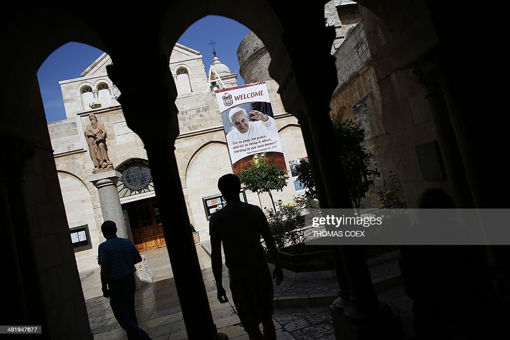 Christian tourists walk past a banner bearing portrait of Pope Francis on May 18, 2014, inside the yard of Saint Catherine Church in the Church of Nativity, in the West Bank Town of Bethlehem.The pope's visit is scheduled to begin in Jordan on May 24, and he is then due to spend two days in the Holy Land from May 25.