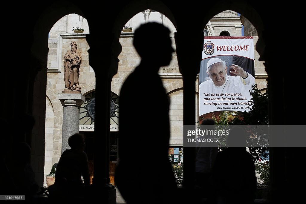 Christian tourists walk past a banner bearing portraits of Pope Francis on May 18, 2014, inside the yard of Saint Catherine Church in the Church of Nativity, in the West Bank Town of Bethlehem.The pope's visit is scheduled to begin in Jordan on May 24, and he is then due to spend two days in the Holy Land from May 25.