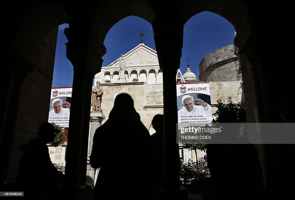 Christian tourists walk past a banner bearing portraits of Pope Francis on May 18, 2014, inside the yard of Saint Catherine Church in the Church of Nativity, in the West Bank Town of Bethlehem.The pope's visit is scheduled to begin in Jordan on May 24, and he is then due to spend two days in the Holy Land from May 25. AFP PHOTO / THOMAS COEX