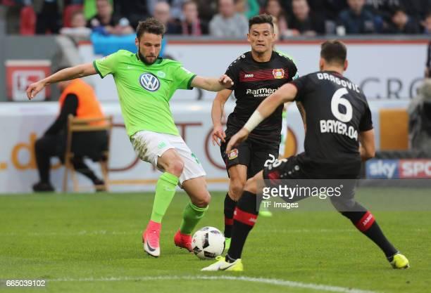 Christian Traesch of Wolfsburg and Charles Aranguiz of Leverkusen and Aleksandar Dragovic of Leverkusen battle for the ball during the Bundesliga...