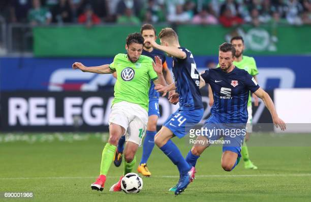 Christian Traesch of Wolfsburg competes with Maximilian Sauer and Quirin Moll of Braunschweig during the Bundesliga Playoff first leg match between...