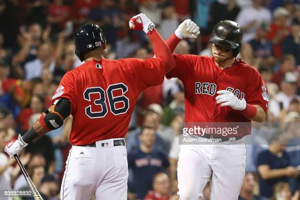 Christian Vazquez high fives Eduardo Nunez of the Boston Red Sox after hitting a solo home run in the fifth inning of a game against the New York...