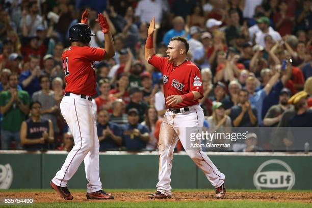 Christian Vazquez high fives Rafael Devers of the Boston Red Sox after scoring in the eighth inning if a game against the New York Yankees at Fenway...